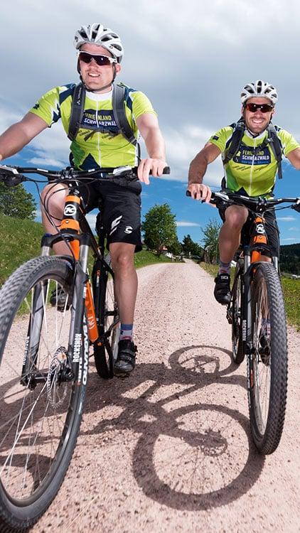 Zwei Mountainbiker auf einem Feldweg bei Furtwangen im Schwarzwald.