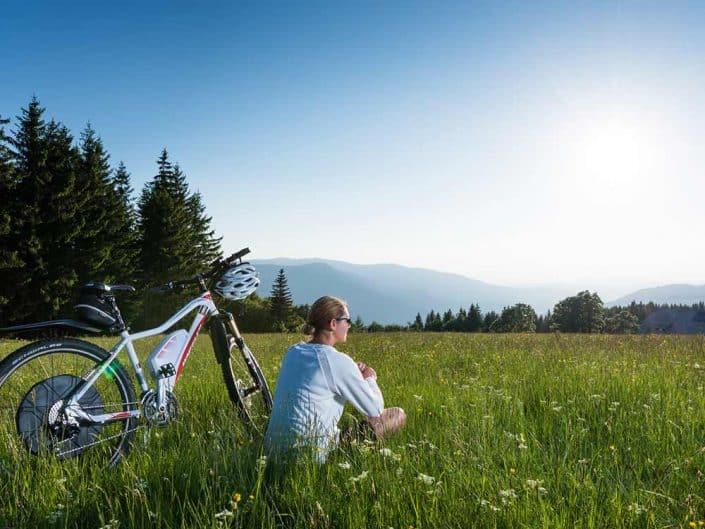 Mountainbikerin macht eine Pause mit ihrem Bike auf einer Wiese bei Furtwangen im Schwarzwald.