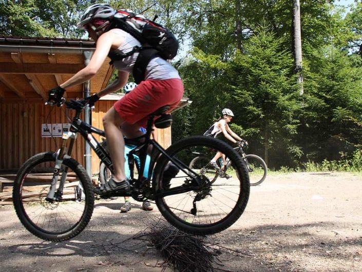 MTB Fahrtechnik Kursteilnehmer (Fortgeschritten) fährt über Hindernis mit seinem Mountainbike.