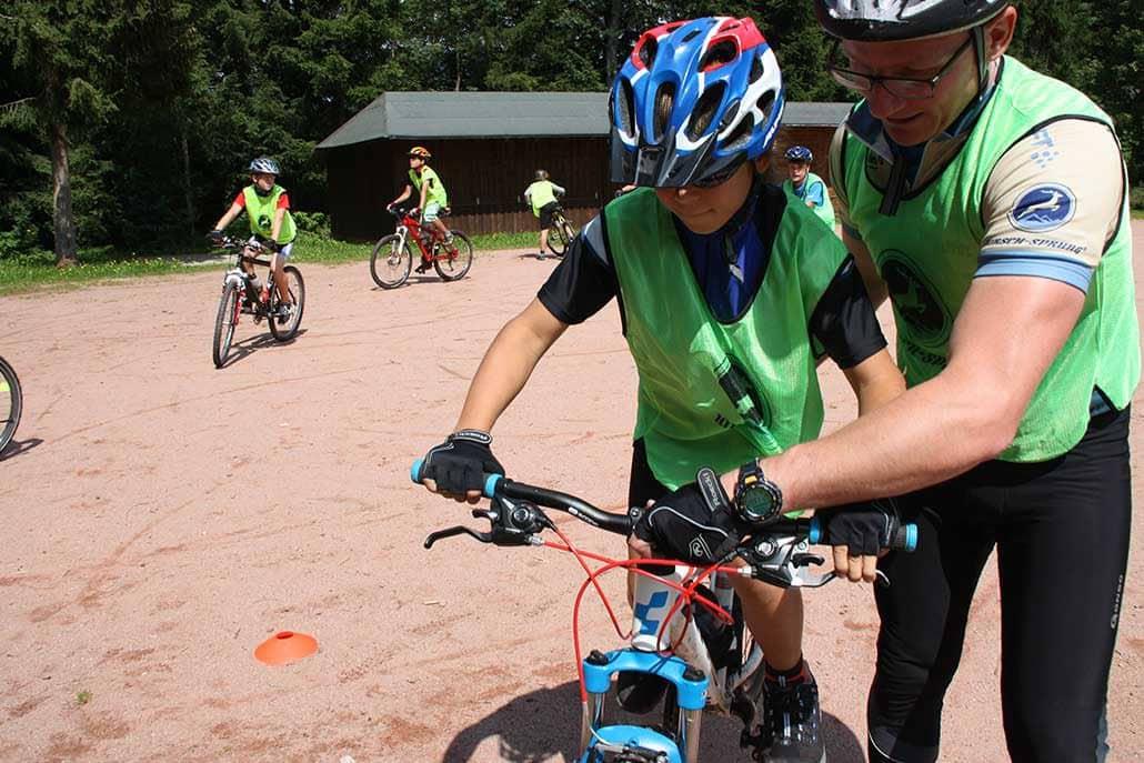 Kind übt Mountainbikefahren mit Guide bei Kindercamp für MTB