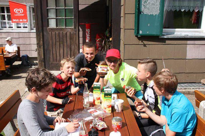 Kinder sitzen mit Guide um den Mittagstisch beim MTB Camp für Kinder.