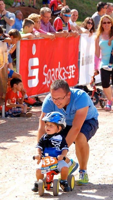 Laufrad Trophy Papa hilft Kind beim Laufrad-Fahren