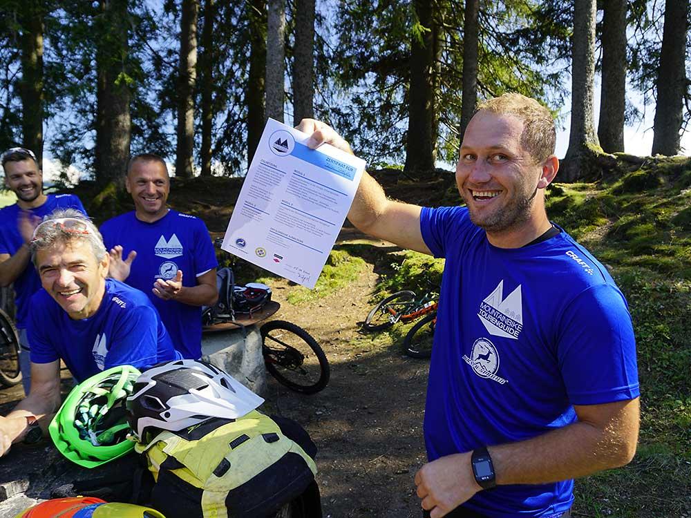 Teilnehmer zeigt das Zertifikat der MTB Guideausbildung